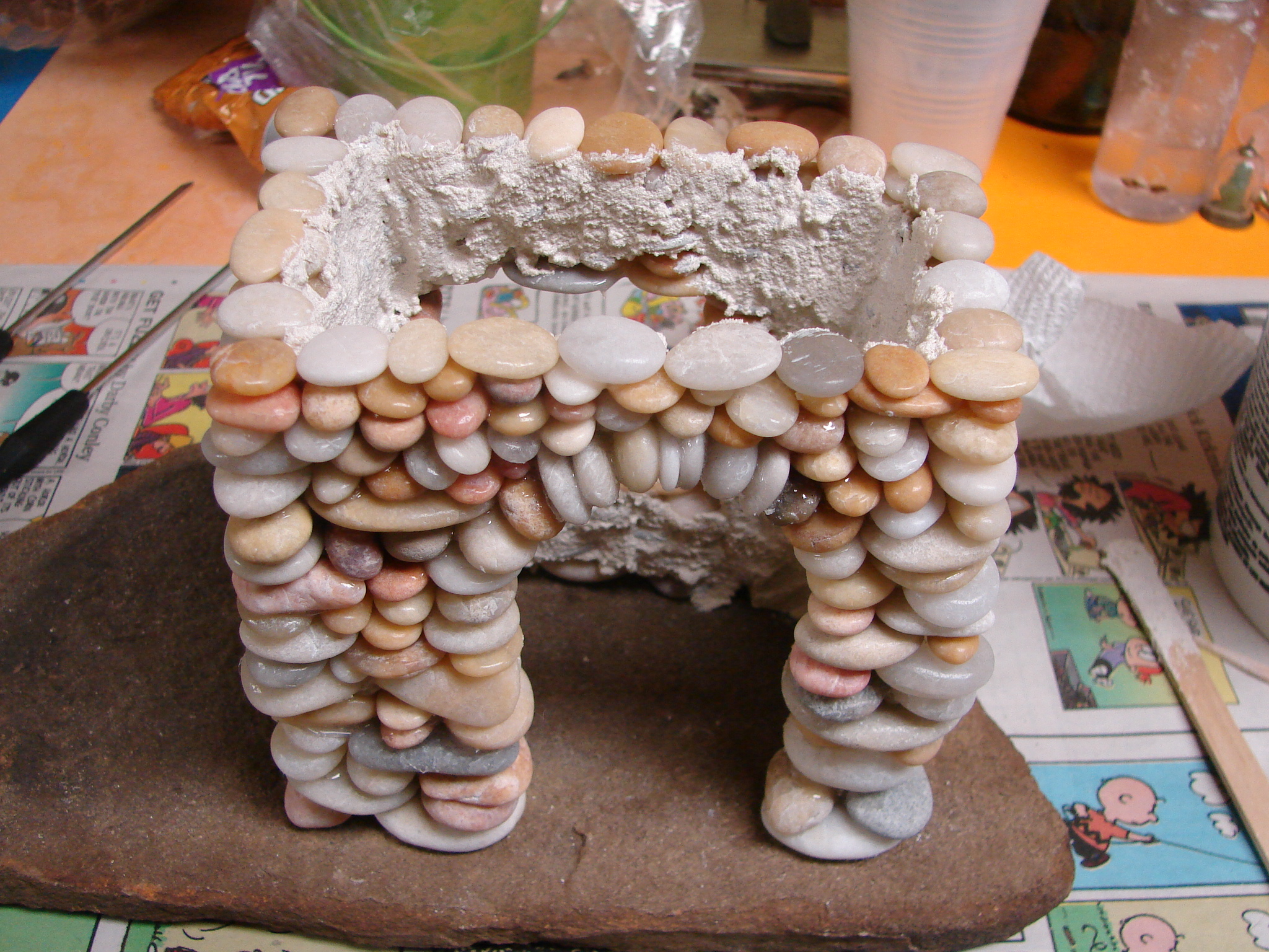 Beach pebble stacked stone fairy house in progress How to make a fairy door out of clay
